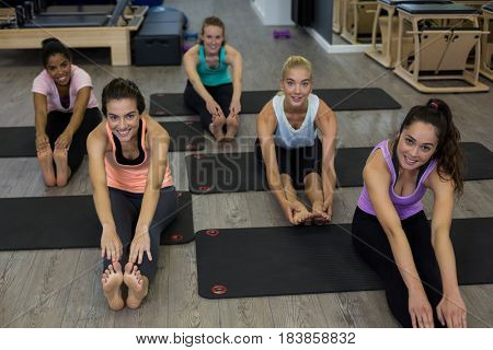 Portrait of smiling women performing stretching exercise in gym