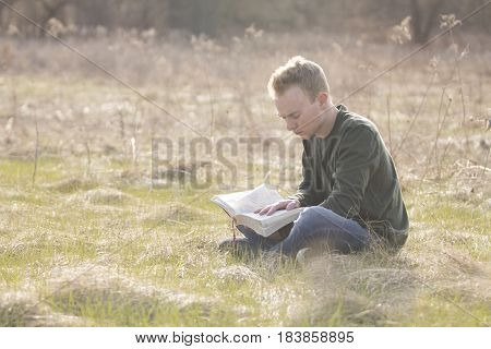 Man reading Bible in open field and studying