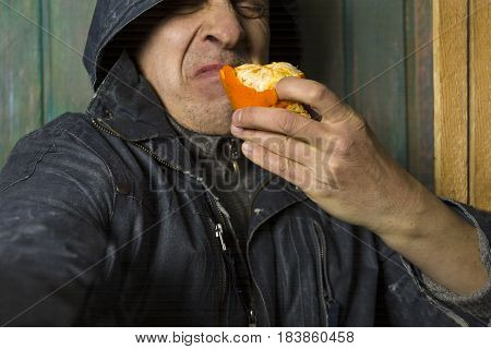 Hooded man tasting a disgusting fruit extremely expressive cropped studio portrait