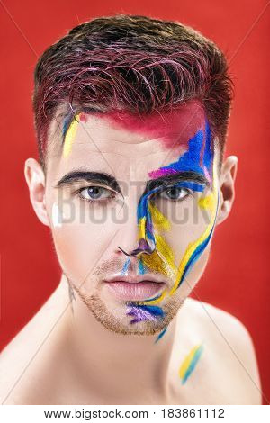 portrait of young attractive man with colored face paint on a red background. Professional Makeup Fashion. fantasy art makeup