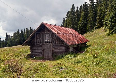 wooden hut on Stredna polana mountain meadow with trees on the background bellow Velky Choc hill in Chocske vrchy mountains in Slovakia