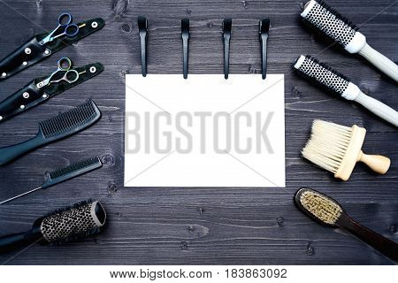 Hairdresser tools on wooden background. Blank card with barber tools flat lay. Top view on wooden table with scissors comb hairbrushes and hairclips with empty white paper free space