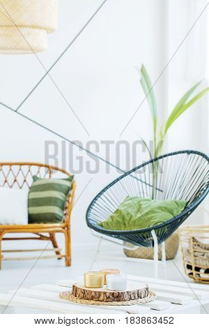 White room with modern round chair and rattan sofa