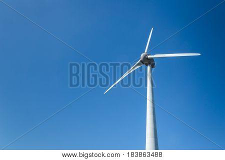 wind energy turbine / modern wind mill against blue sky background