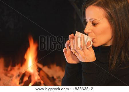 Pretty woman drinking a cup of hot drink near the hearth