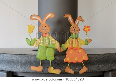 Friendly Easter bunnies hold flowers and sit on stove