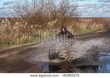 ATV race dirty road. Uncnown driver in water and mud. Offroad extreme mud covered wet racer