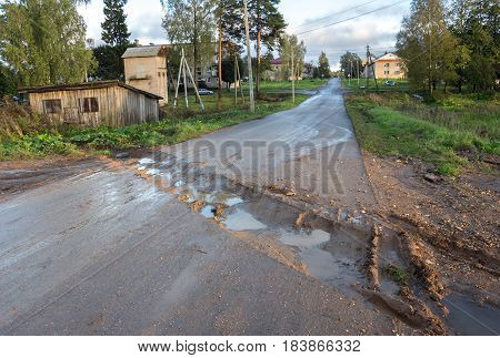 Rural road. Rut with puddles. Countryside landscape