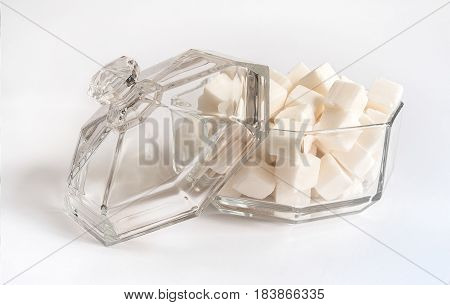 Lump sugar. Glass sugar bowl with lid on white background