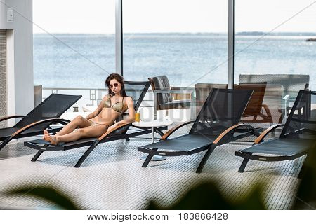 Young attractive slim girl in bikini relaxing on deck chair in wellness spa hotel resort. Near the table is a glass of orange juice