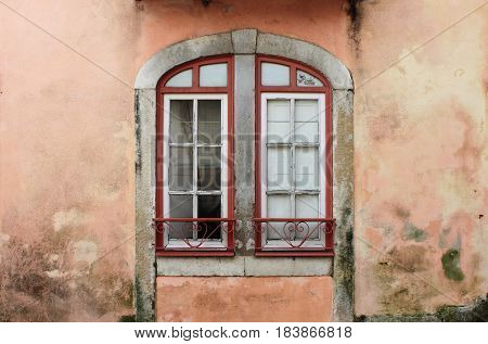 Old arched window with a crumbling wall