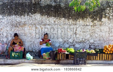 VALLODLID MEXICO - FEBRUARY 11: Two women sell fruit and vegetables on the sidewalk in Valladolid Mexico on February 11 2017