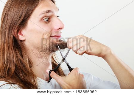 Cut and shave concept. Young man with long beard holding scissors. Boy cutting hair on chin.