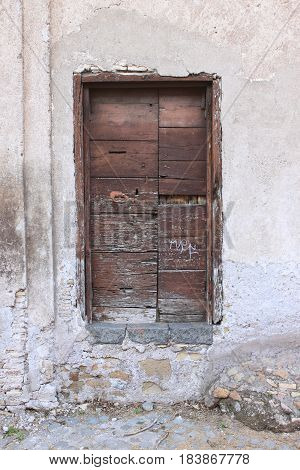 An ancient and weathered wooden door on a crumbling wall