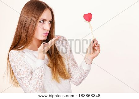 Valentine's day gift concept. Beautiful woman holding love sign heart shaped wooden hand stick sending air kiss studio shot on white background