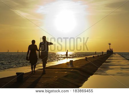 A loving couple walking along the pier at sunset. Saint Joseph Lake Michigan.
