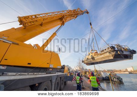 MOSCOW - NOV 21, 2016: Lifting of ship with crane to shore for organization of inter-navigational sludge and repairs during closure of navigation of Mosvodostok technical fleet