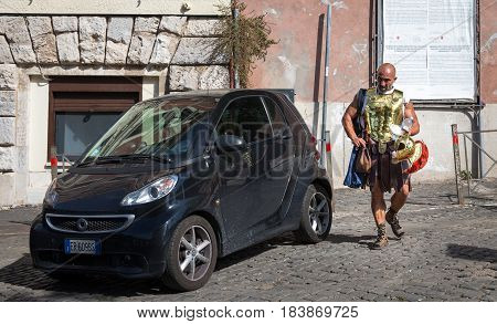 ROME ITALY - July 27 2015: A Roman Gladiator street performer heads to work after donning his costume near the Colosseum. Gladiators are ubiquitous in Rome charging tourist a fee for having their pictures taken with them.