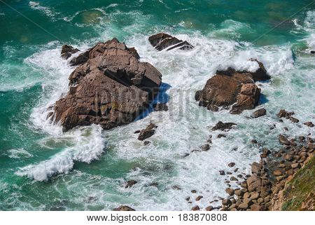 Aerial view of green sea water with waves smashing on the rocky coast