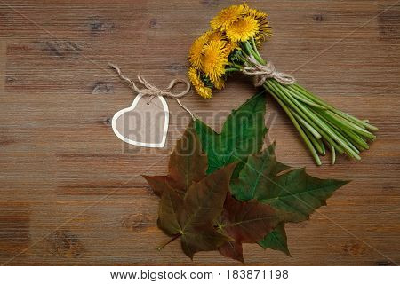 Posy of Yellow Dandelions.Heart Wish Card.Green Leaves.Garden's Background.Wooden Table.Top View