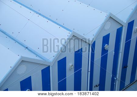 White and blue beach changing huts forming diagonal zigzag shape background