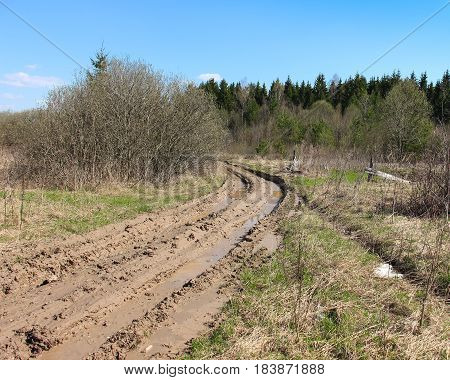 Countryside road. Dirty rut with puddles. Deep furrows