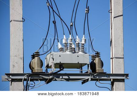 Electrical junction box with insulators on background of blue sky. Close-up