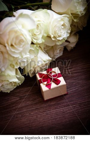 Wedding composition set-up on wooden with rings gift wrap box and roses flower bouquet