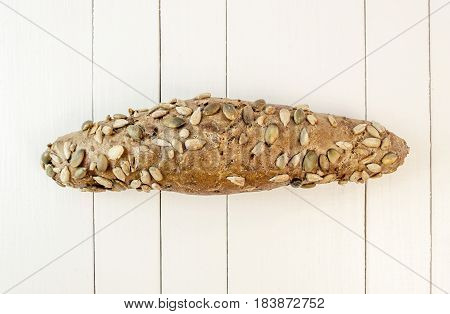 Overhead view of freshly baked dietary bread roll on a white table