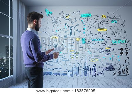 Young businessman with document in hand standing in concrete room with night city view and business sketch on wall. Research concept. 3D Rendering