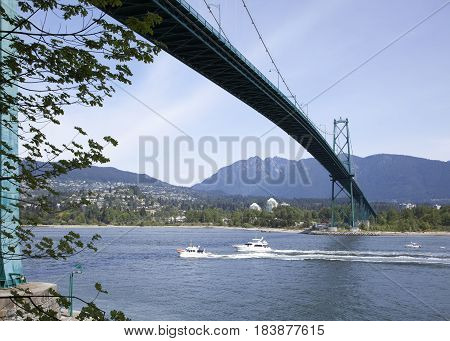 Boats passing by under Lions Gate Bridge in Vancouver Harbour (British Columbia Canada).