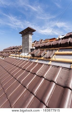 A roof under construction with stacks of roof tiles ready to fasten