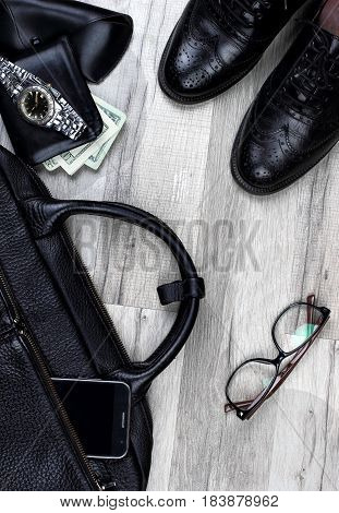 Man accessories in business style. Briefcase, brogues , shoes, wallet with money and other luxury businessman attributes on leather black background, fashion industry, top view.Copy space
