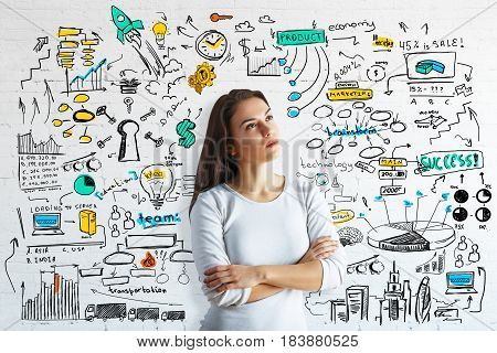 Thoughtful young european woman on brick background with colorful business sketch. Solution concept