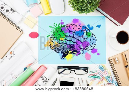 Top view of messy office desktop with coffee cup supplies and colorful brain sketch. Creative mind concept