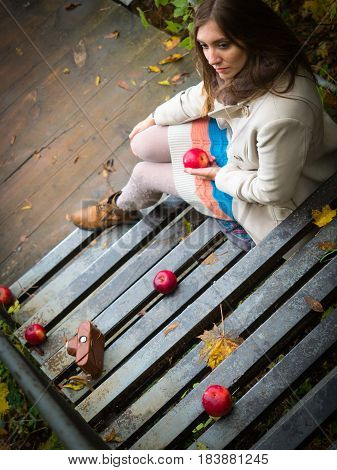 Girl sitting down the stairs with apples.