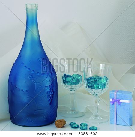 Still life simulating solidified drink in glasses and empty bottle.