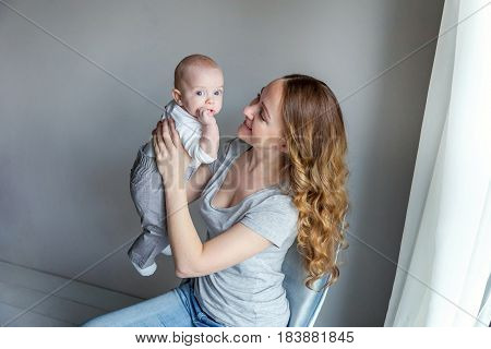 Young mother holding her newborn child. Woman and new born boy relax in a white bedroom with blue chair. Mother breast feeding baby. Family at home