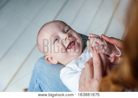 Newborn child lies on his mother's lap. Mother holding her newborn child. Woman and new born boy relax in a white bedroom. Mother breast feeding baby. Family at home