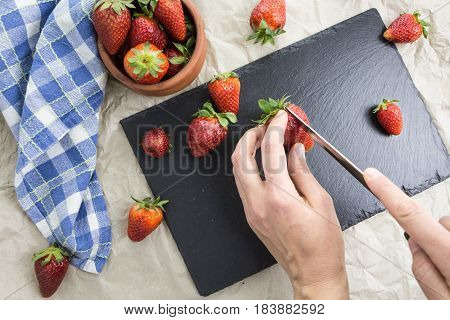 Hands Slicing Red Ripe Strawberries, With Bowl And Kitchen Towel On A Table.