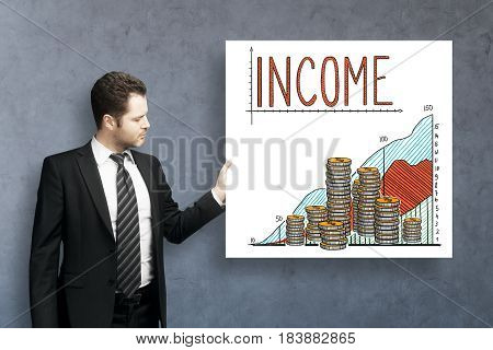 Handsome young businessman on concrete background with income sketch on poster