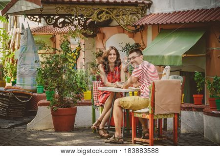Young Beautiful Happy Loving Couple Sitting At Street Open-air Cafe Looking At Camera. Beginning Of