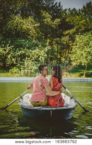 Young Beautiful Happy Loving Couple Rowing A Small Boat On A Lake. A Fun Date In Nature. Couple Hugg