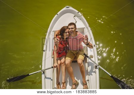 Top View Of Happy Loving Couple Rowing A Small Boat On A Lake. A Fun Date In Nature. Couple Hugging