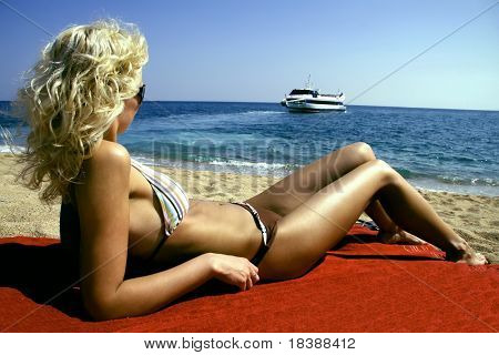 Beautiful young and slender woman model relaxing on beach and watching a ship on sea. Costa Brava beach.