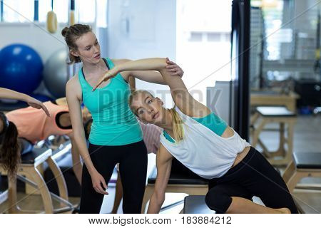 Female trainer assisting woman with exercise in gym
