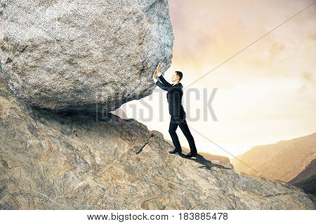 Side view of young businessman pushing huge rock up mountain. Beautiful background. Effort concept poster