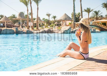 Beautiful Woman In Bikini And Sunlasses Sitting In Swimming Pool With Cocktail.