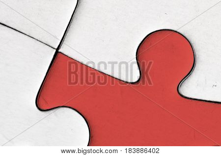 close up of a red jigsaw piece surrounded by white pieces. resemble a human figure. solidarity. symbol. man.