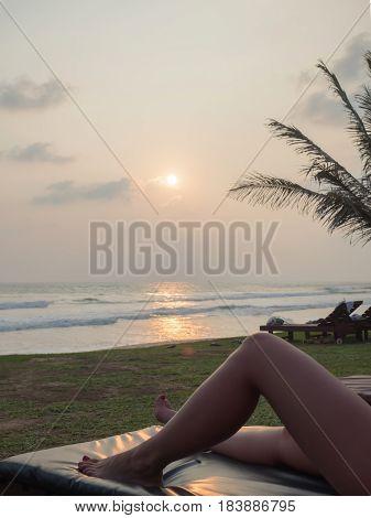 gilr's legs on lounge on the beach